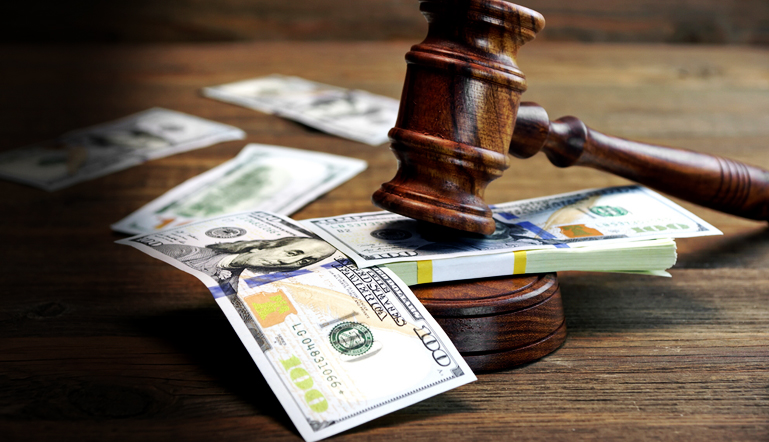 A gavel on the table in a court along with dollar bill during a bankruptcy case followed by Find Your lawyer 911