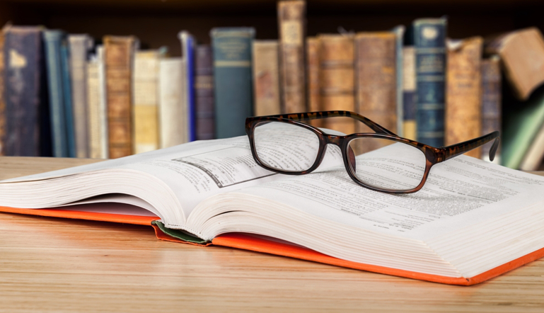 Pair of glasses on a book at a table in our library at Find Your Lawyer 911