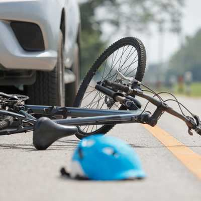 A bicycle falling on the road after an accident with a car along with a helmet