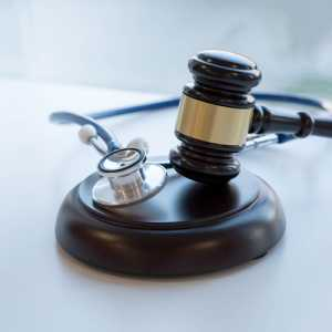 A gavel and a stethoscope on a table