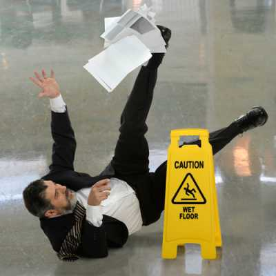 A gentleman falling on the wet floor while his documents are dropping