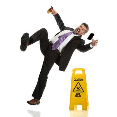 A gentleman holding a coffee mug and his cellphone just falling due to a wet floor