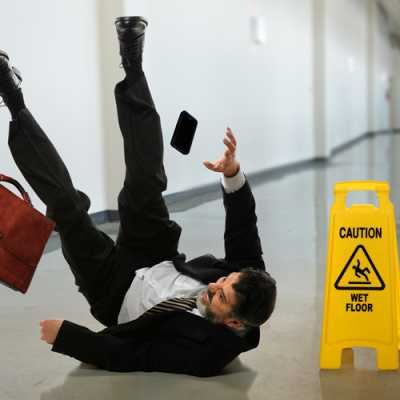 A gentleman just slipped from a wet floor and falling on the floor. His bag and mobile phone are also falling