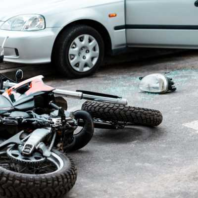 A motorcycle and a car just after the accident while the bike is falling on the road