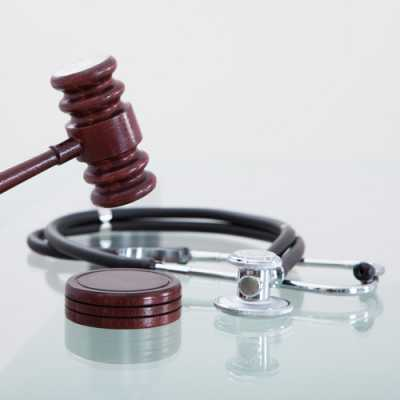 A stethoscope and a gavel at a table in Jaloudi & Associates Clifton NJ