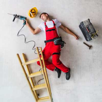 A worker is lying on the floor unconsciously, and all his tools are also falling there