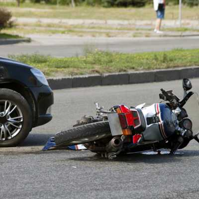 An accident between a car and a motorcycle on the road while the bike is falling on the way