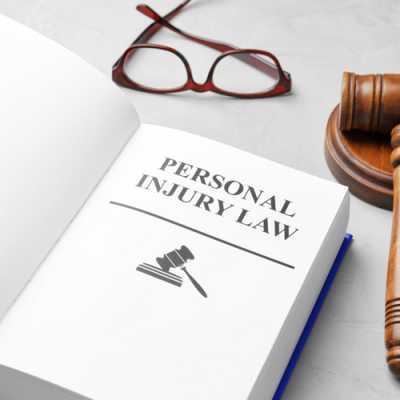 Book of personal injury law along with a gavel and glasses on the table