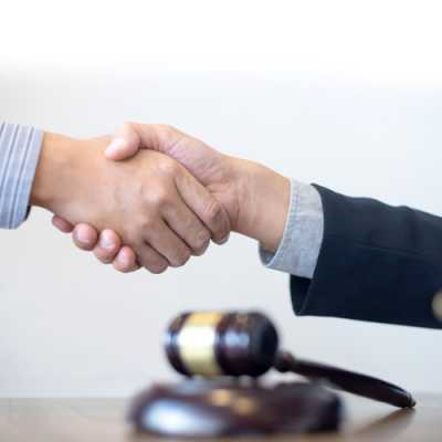Lawyer and a client are shaking hand while A gavel is at the table at Law Offices Of Daniel Santiago Clifton NJ