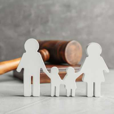 Model of a family with the background of a gavel on the table at Degrado Halkovich LLC Hackensack NJ
