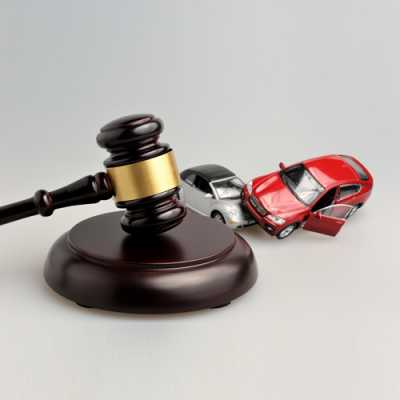 Models of two cars hitting with each other along with A gavel in Calcagno And Associates Westfield NJ