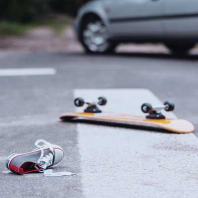 The shoe of a boy a rolling pad falling on a road near a car