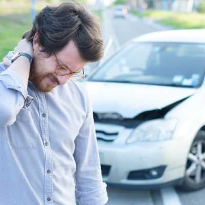 Young man feeling severe neck and back pain after an accident with a car