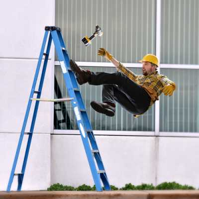 a worker at his construction site slipping and falling on the ground from the portable staircase