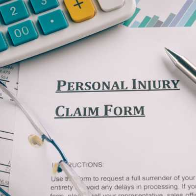 personal injury claim form with a pen, glasses and a calculator at Jaloudi & Associates Clifton NJ