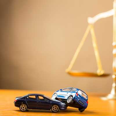 two car models hitting each other and there is a gavel on the table at Harrell, Smith & Williams Metuchen NJ